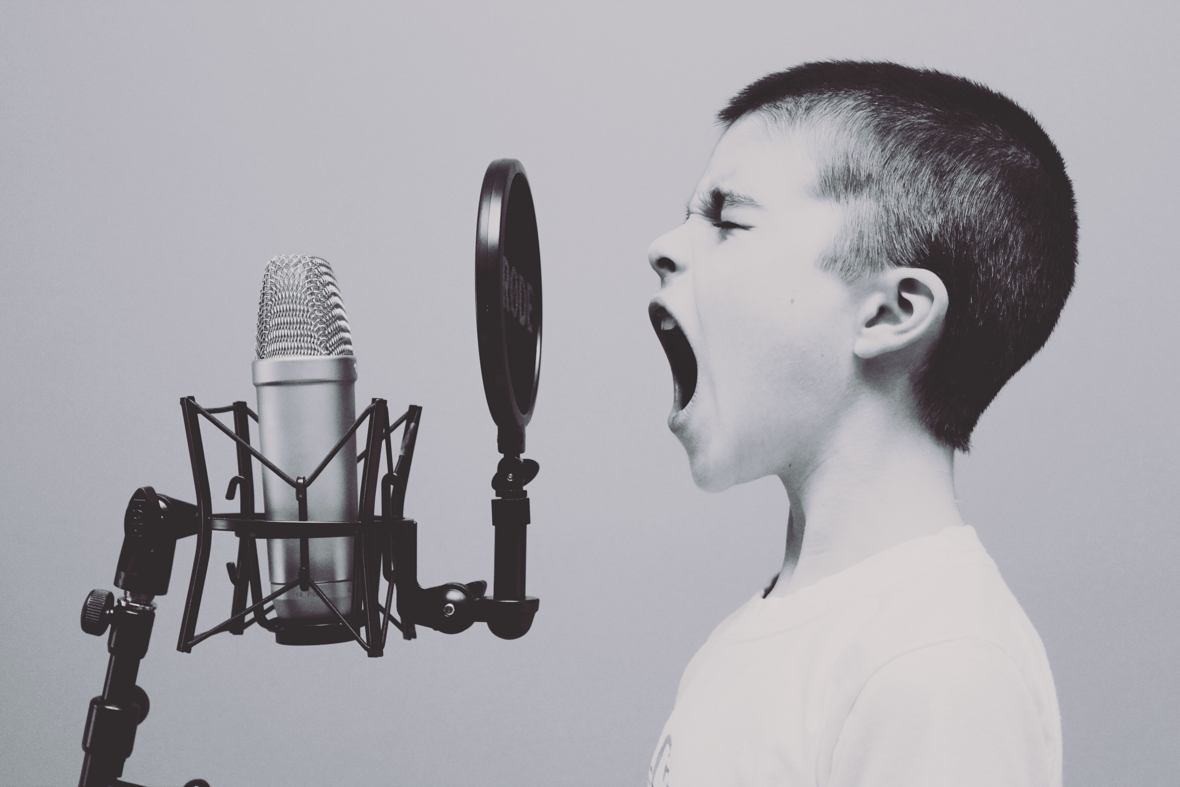 A black and white image of a young boy, eyes closed, singingly loudly into a microphone.