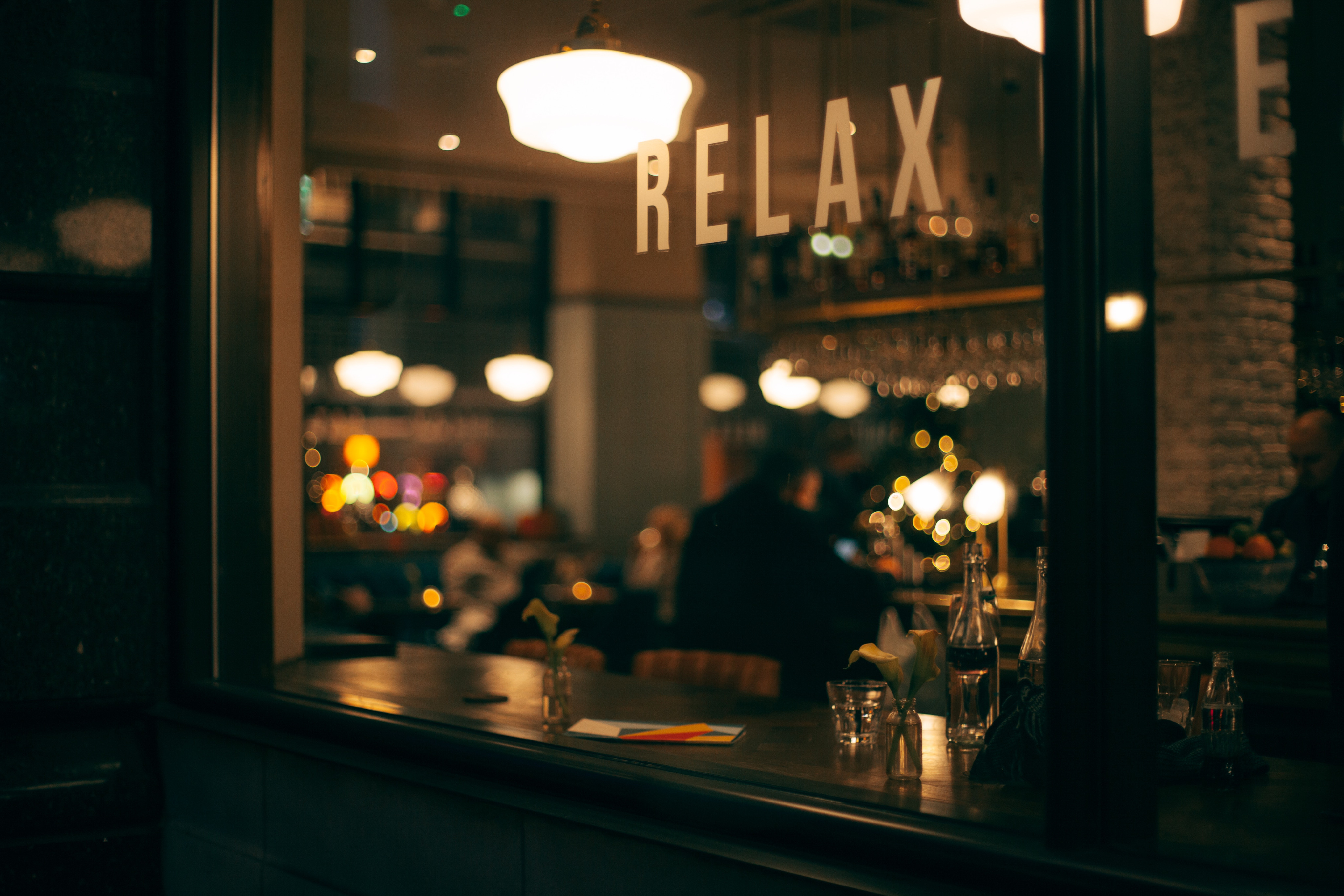 Looking into the window of a restaurant at nighttime with the word Relax painted on the window.