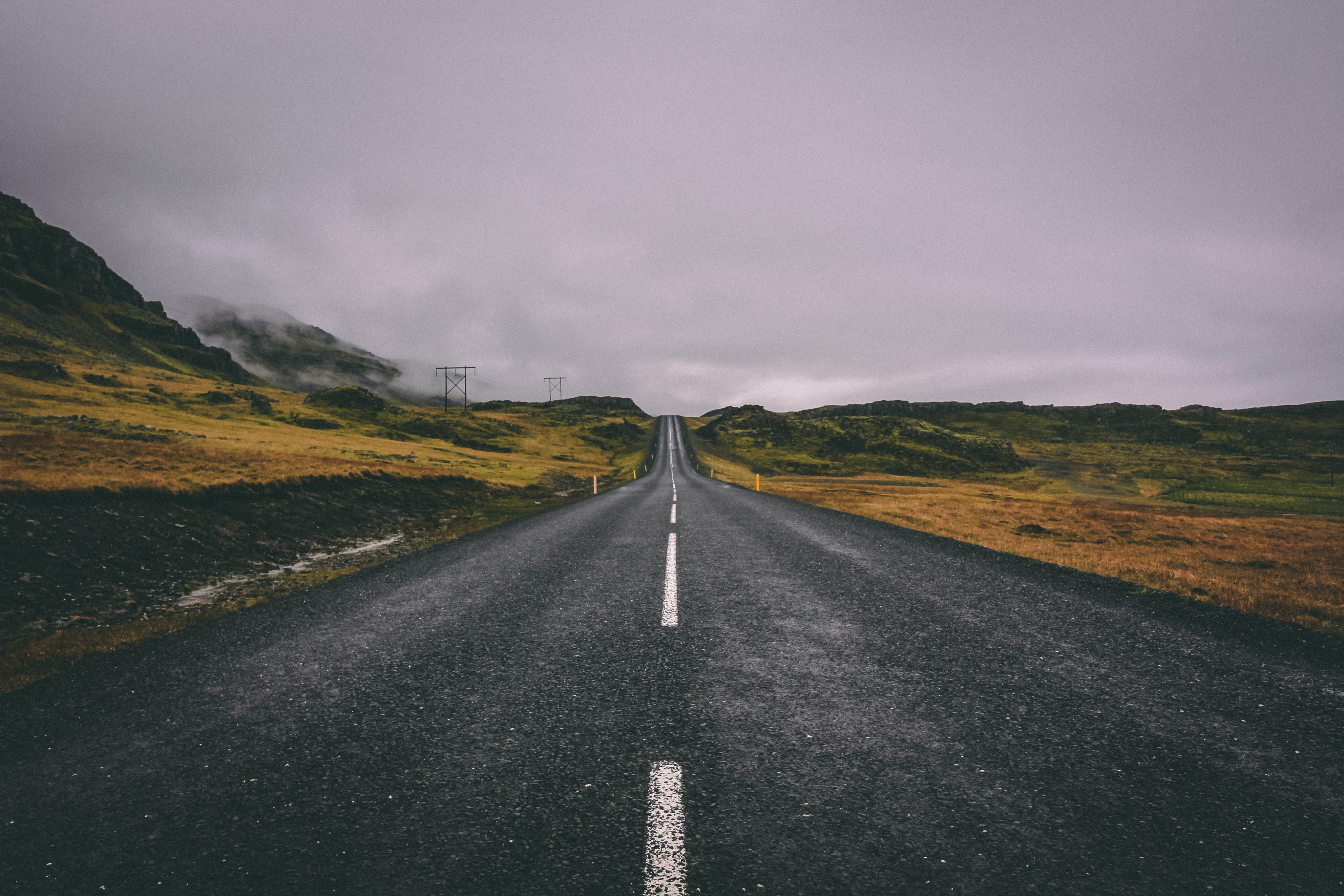 Looking at the horizon of a brown and green landscape from the center of a newly paved road under an overcast sky.