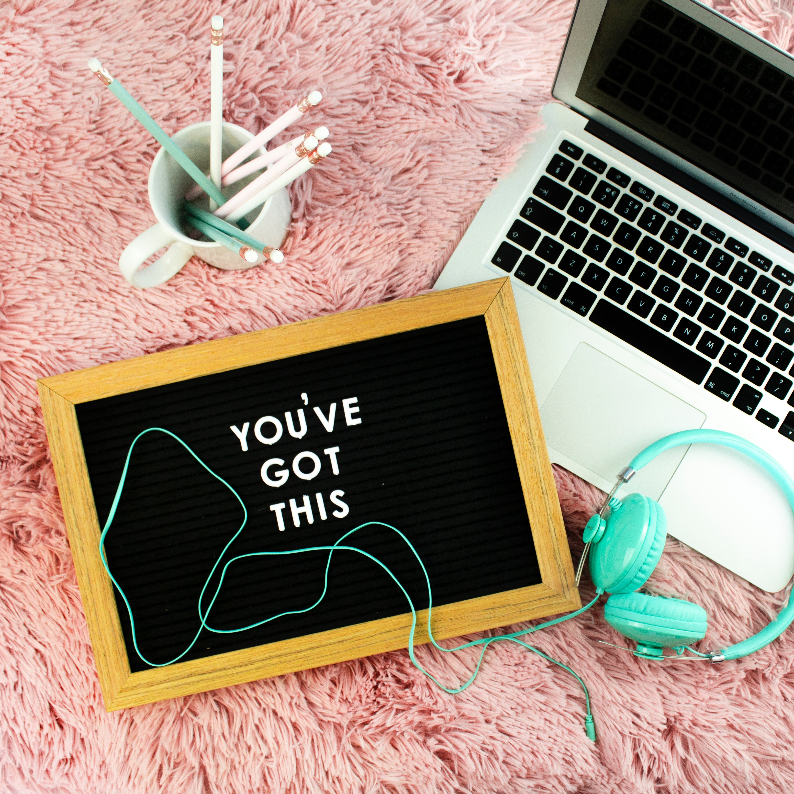 "A laptop, mug of pencils, headphones, and a sign with the words ""You've got this"" sitting on a fluffy pink rug."