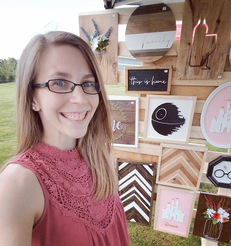 Shauna standing with her art display