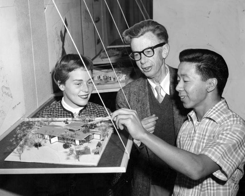 """""""Young Woo, right, of 16411 Plummer St., San Fernando, student at USC School of Architecture, shows model of home he designed to Prof. Clayton M. Baldwin and Jean Johnston, USC student. Model won special mention from architectural school."""" Valley Times, December 22, 1955 – image courtesy of the Valley Times Photo Collection, Los Angeles Public Library."""