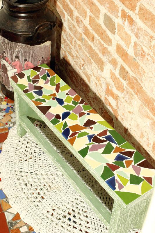 Mosaico para banco com cacos de azulejos coloridos. Artesanato despojado