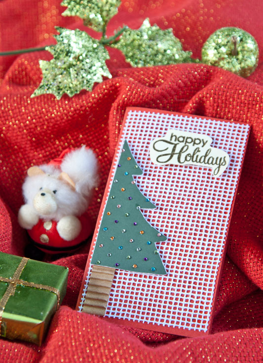 Artesã compõe cartão de Natal de scrapbooking
