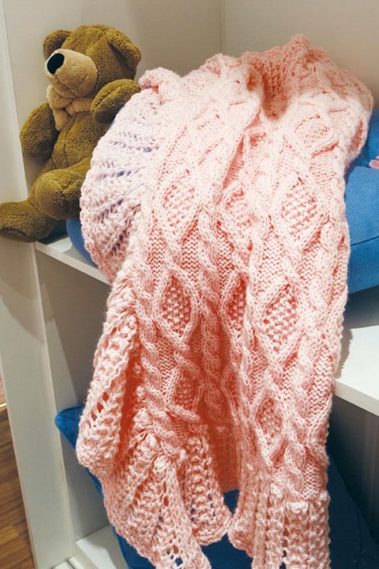 Manta rosa de tricô em ponto irlandês com barrado em crochê