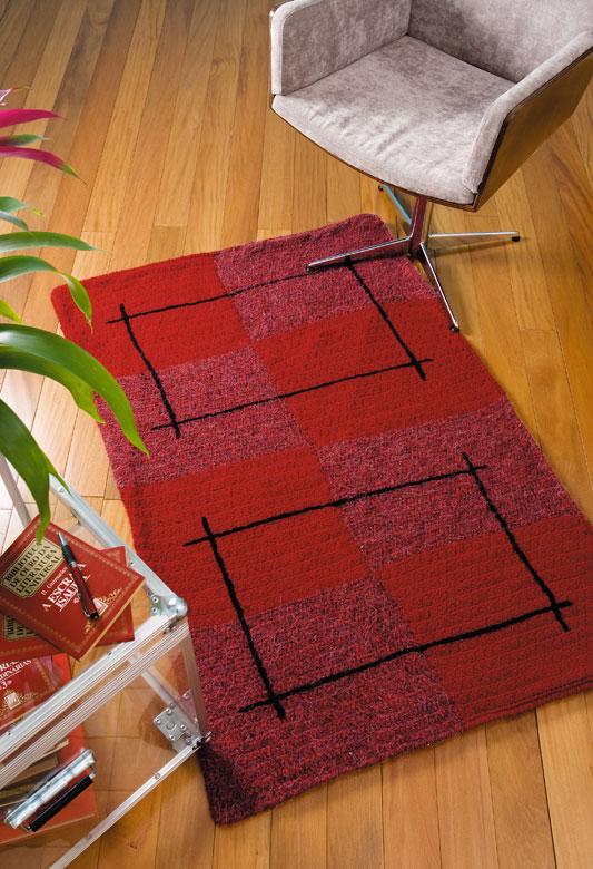 Tapete de crochê com motivos quadrados e tons de vermelho