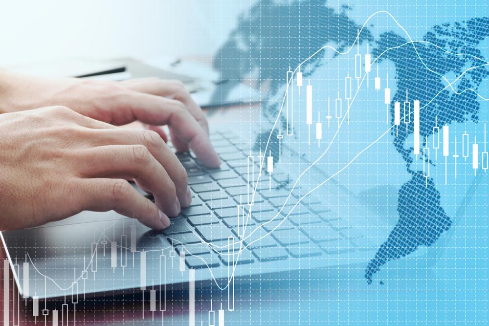 価格チャートを背景にFXの1000通貨取引をパソコンで行っている人