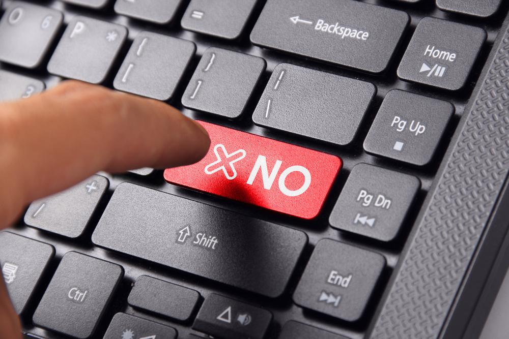 fx_経費_NOと書かれたキーボードを打とうとしている指