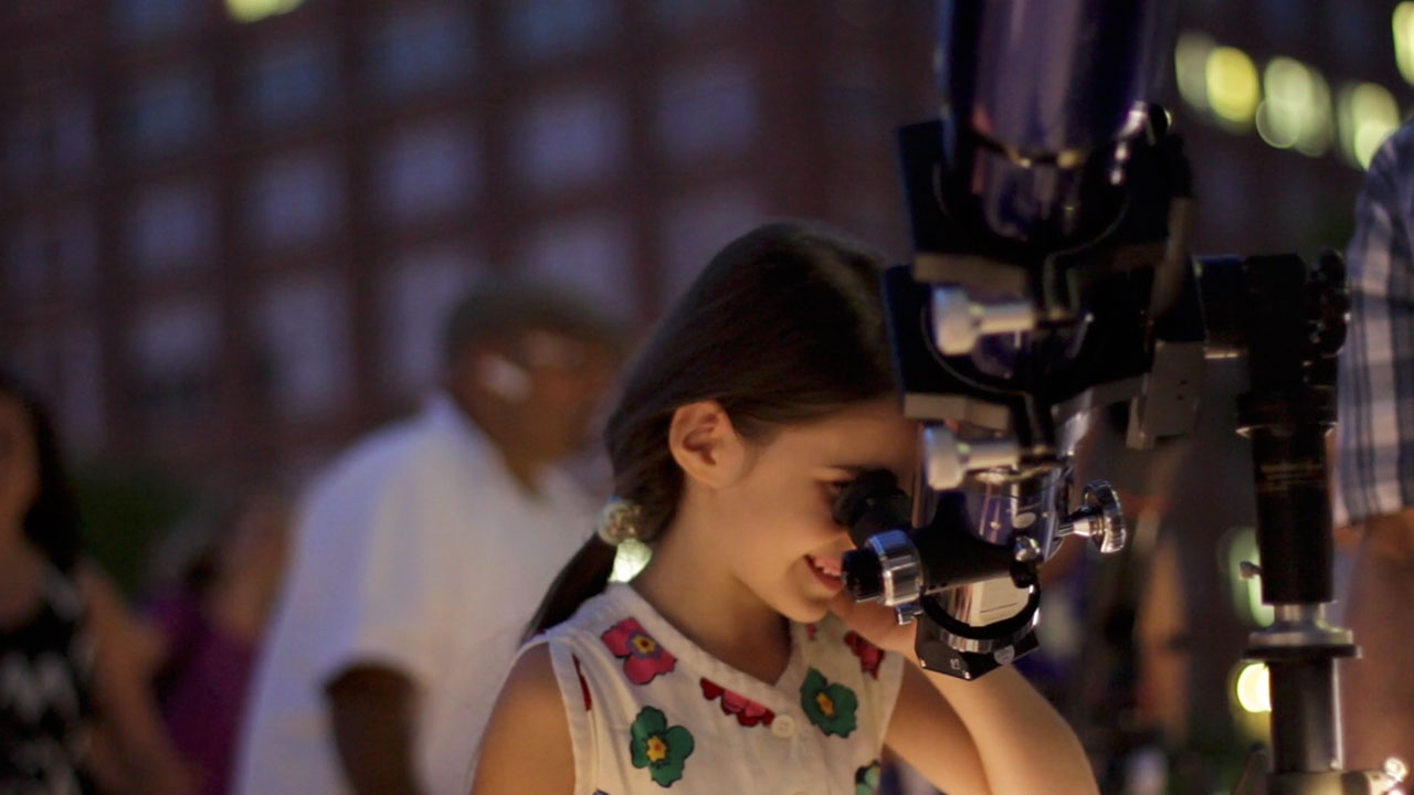 Young Girl Looks through a Telescope