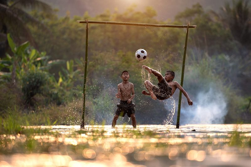 Two boys playing football in a makeshift goal made of bamboo canes.