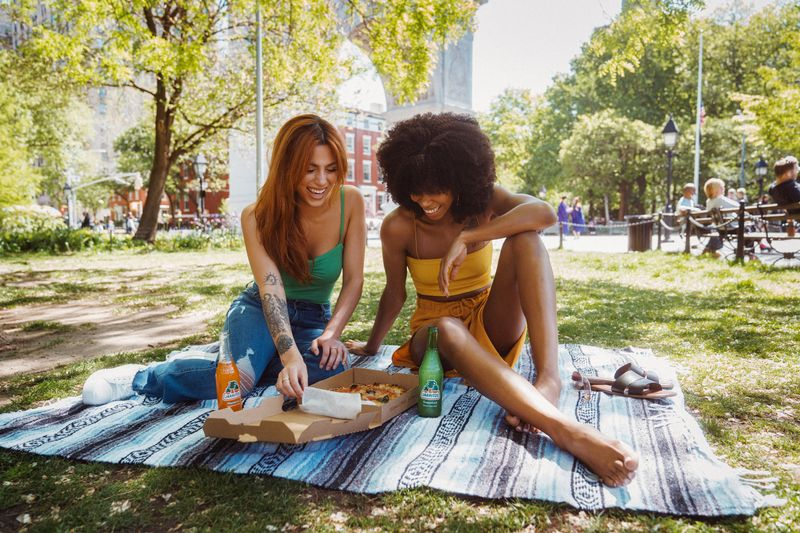 two friends laughing while having a picnic