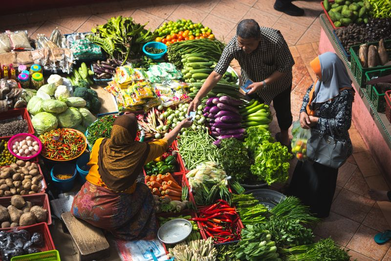 A woman is sitting around lots of fruits and vegetables. She is taking money from a man.