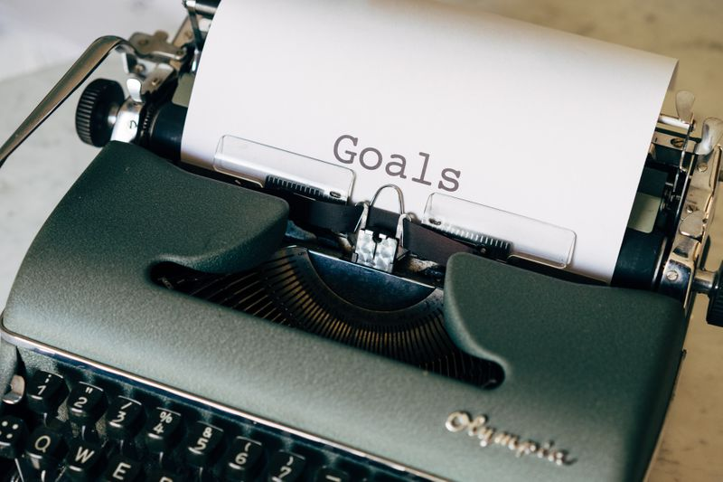 """A typewriter with """"Goals"""" printed on a piece of paper. (Photo by Markus Winkler on Unsplash)"""