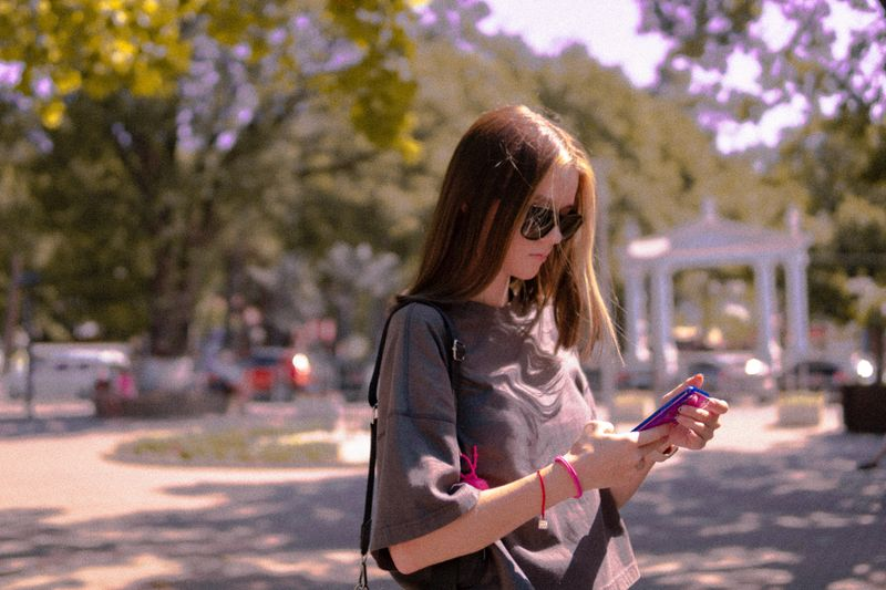 A woman stands outside and looks at her phone