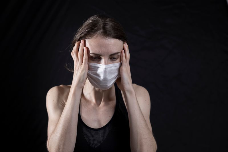 A person wearing a medical mask looking stressed