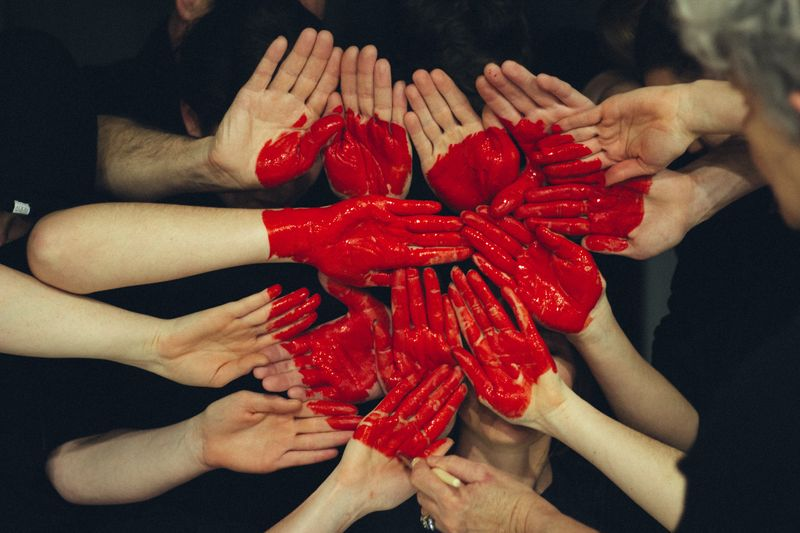 Red heart painted over a bunch of people's hands