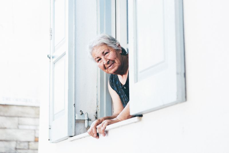 An elderly woman looking out of a window