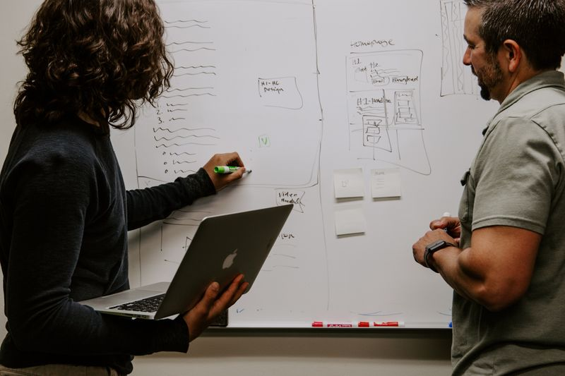 two people writing on a whiteboard