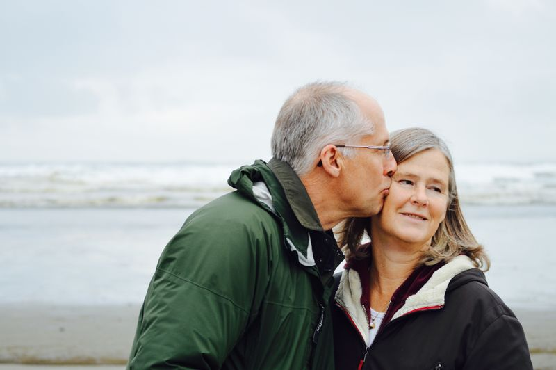 Photo of older man kissing older woman on side of her face.