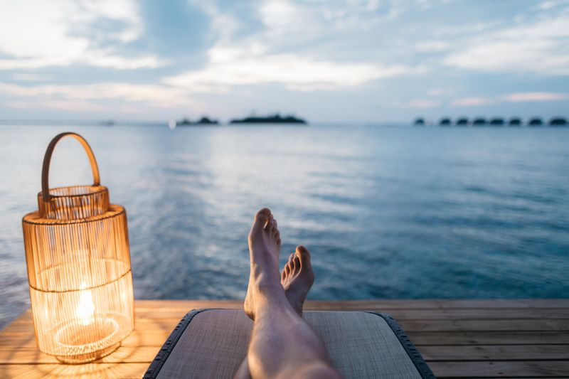 picture of someones feet as they relax on a dock overlooking a lake