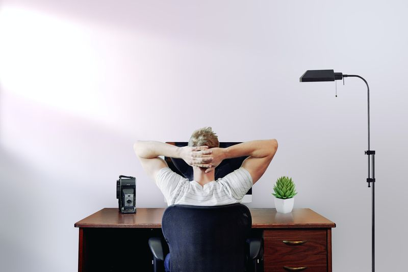 Back view of a man stretching in his chair, looking at his computer