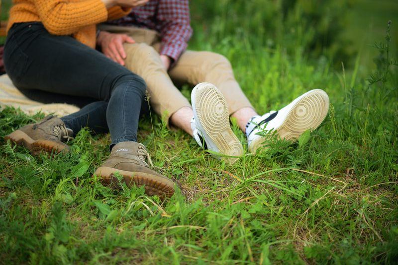 Lovers sitting in a field.
