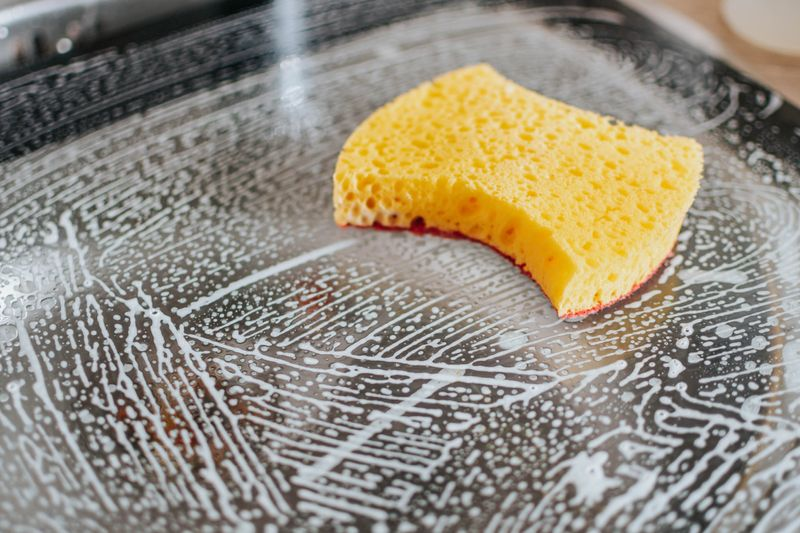 Bright yellow sponge on top of a soapy surface
