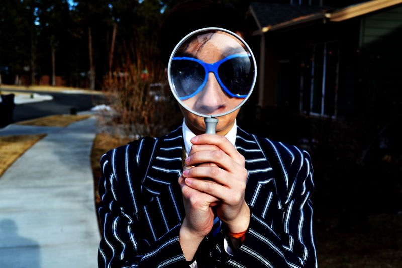 Person looking through a magnifying glass