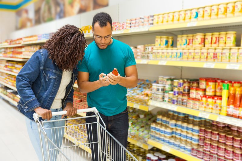 Young couple standing in a grocery store near shelves with canned goods, reading a food label