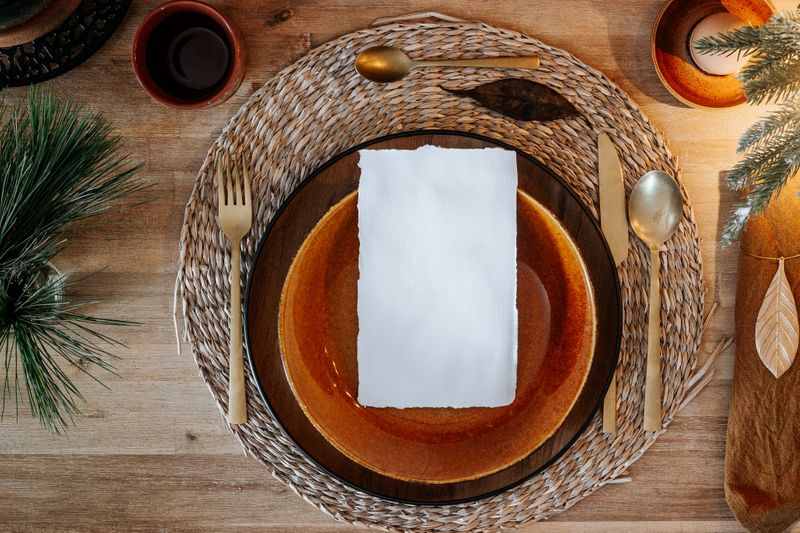 Empty place setting at a table decorated for the holidays.