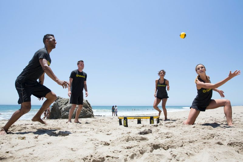 Four players playing Spikeball on a beach