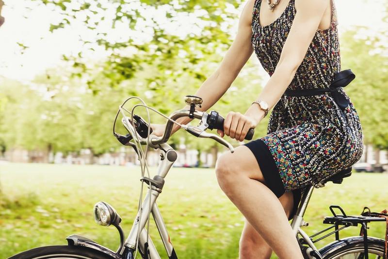 A woman riding a cruiser bike through a park