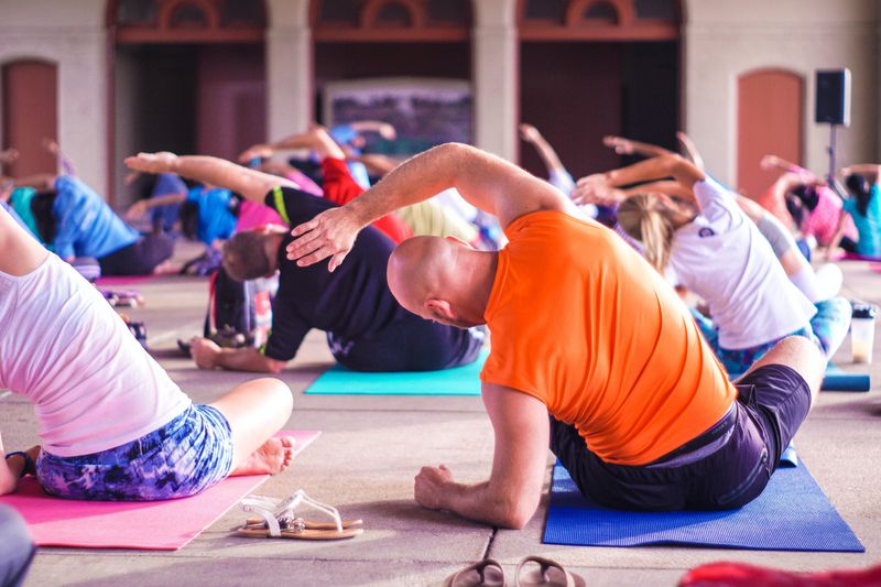 people practicing yoga, sitting cross-legged, leaning on their left elbow and stretching their right arm over to the left
