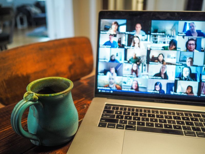 A laptop open to a virtual meeting with several people on screen