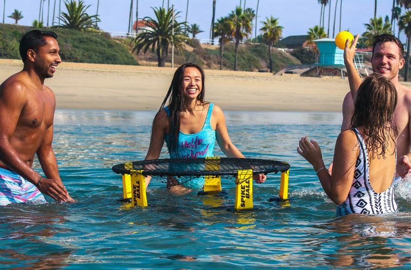 Playing Spikeball at a beach in the water