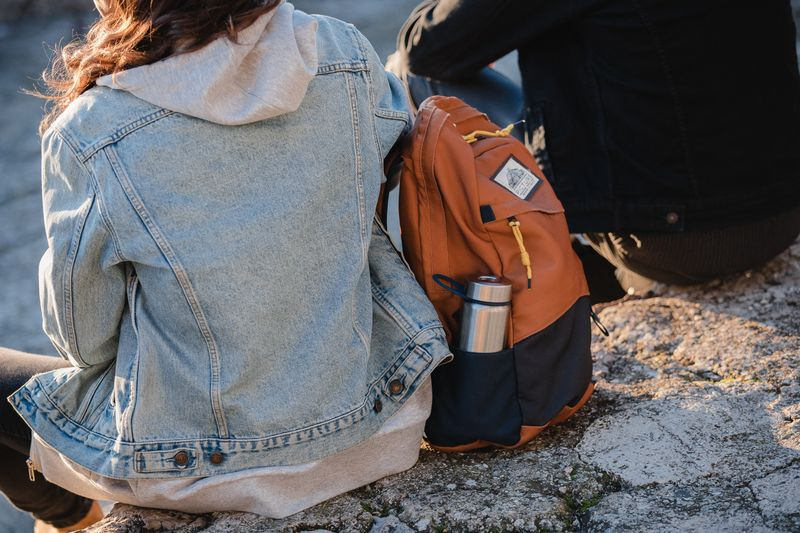 Student sitting outside with an orange knapsack with a water bottle
