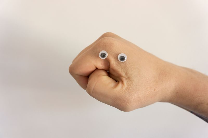 A hand with googly eyes that looks like a worried face