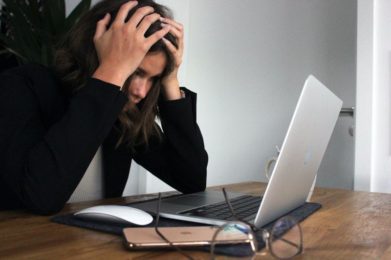 Girl who is stressed with her hands on her head staring at her computer.