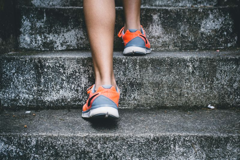 legs with running shoes walking up concrete steps