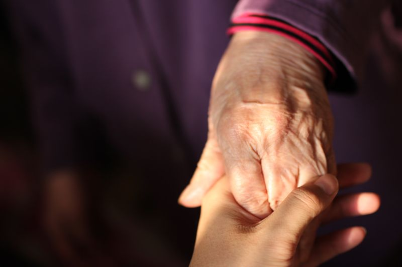 A younger person holding an older person's hand