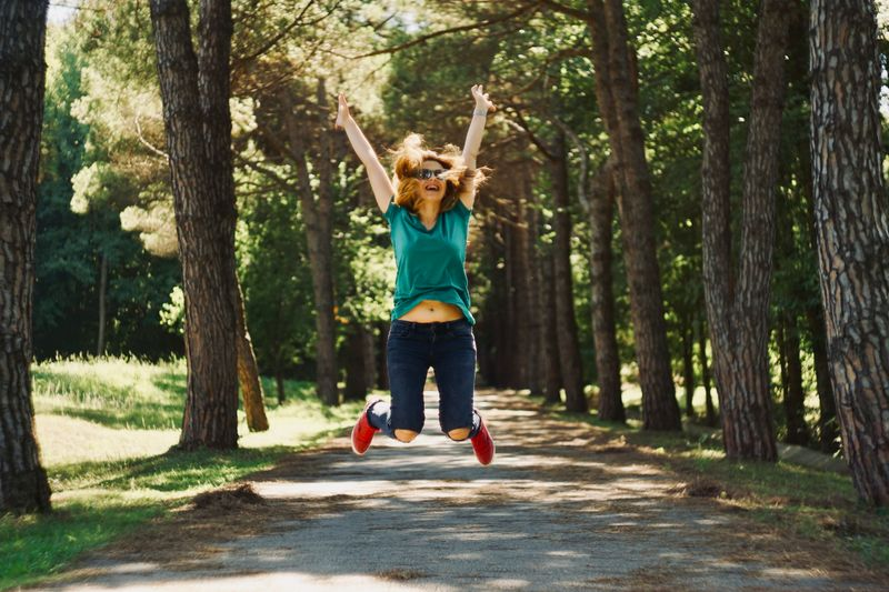 Woman jumping in the air with her arms up
