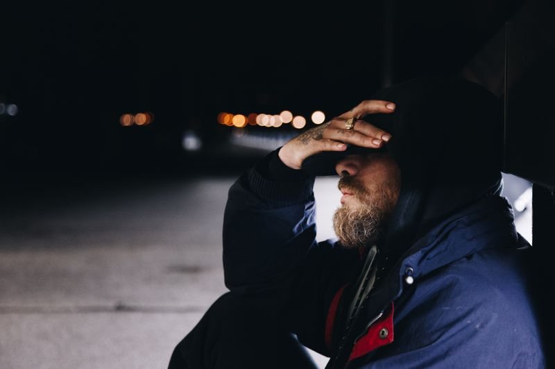 Man sitting alone on sidewalk cradling his forehead in his hand.