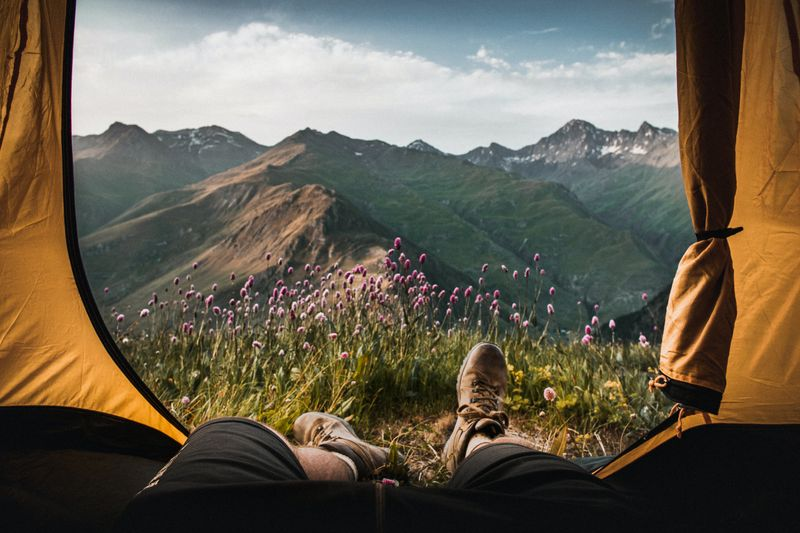 A person hangs their feet out of a tent facing a mountain view