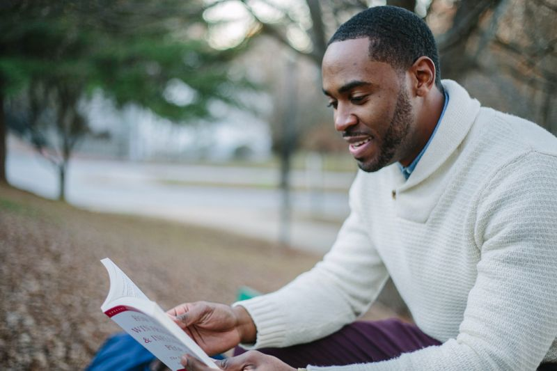A person in a field reviewing an investment guide