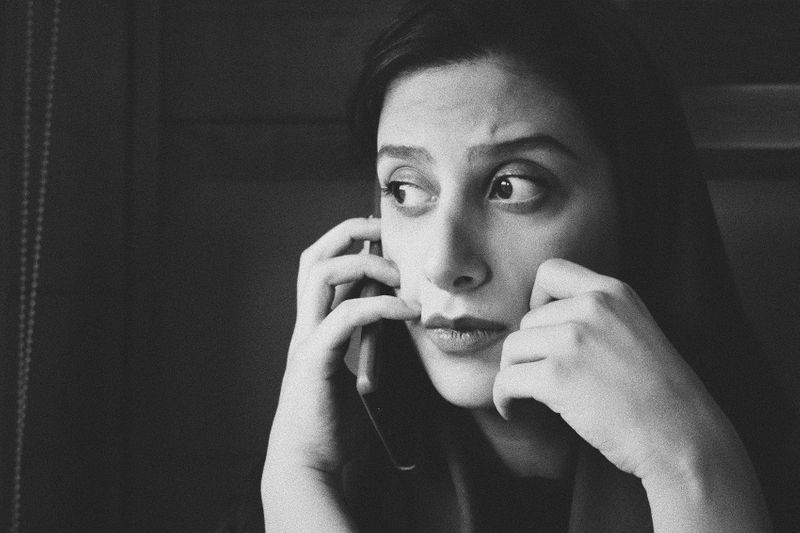 A woman on her cell phone looking worried.