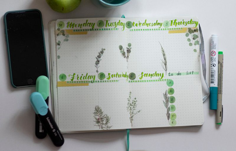 a phone and notebook calendar with light blue and green pens and markers surrounding it