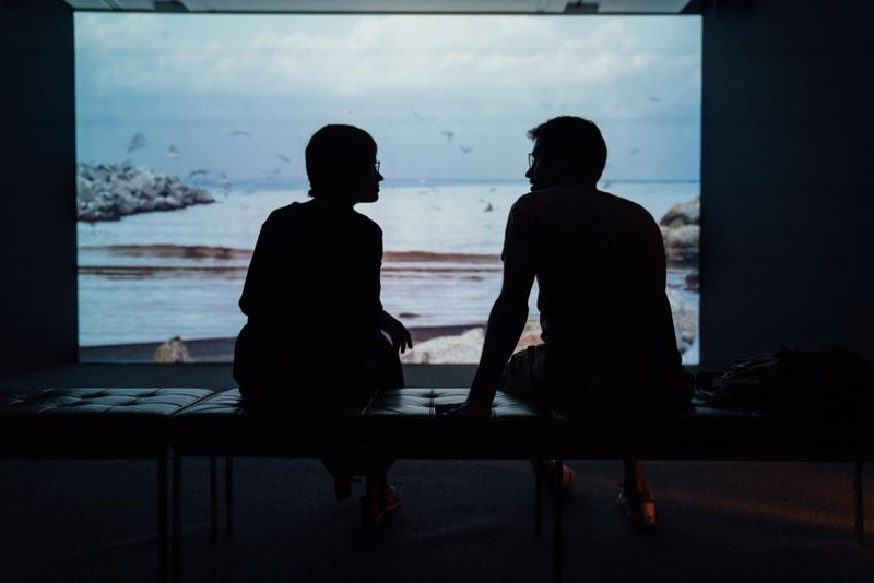 a couple is sitting in shadow talking in front of a large screen