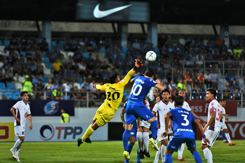 Action shot of a football match with two players competing for the ball.