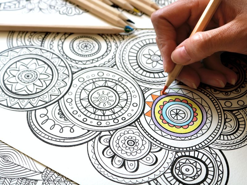 A person, filling in patterns of a Mandala with an orange pencil crayon