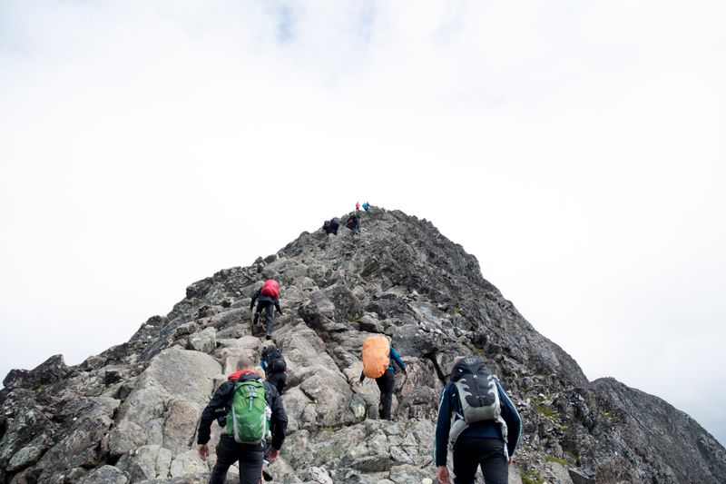 A mountain guide leading others up a mountain.